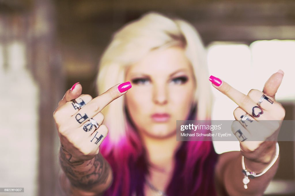 Beautiful Woman With Tattooed Hands Giving Obscene Gesture : Stock Photo