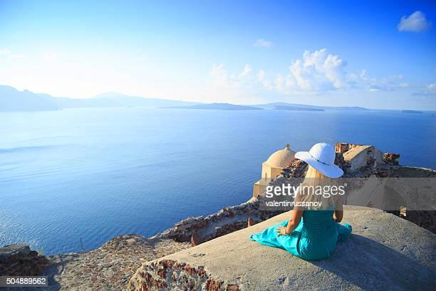 Schöne Frau mit türkisfarbenen Kleid in Santorin, Griechenland.