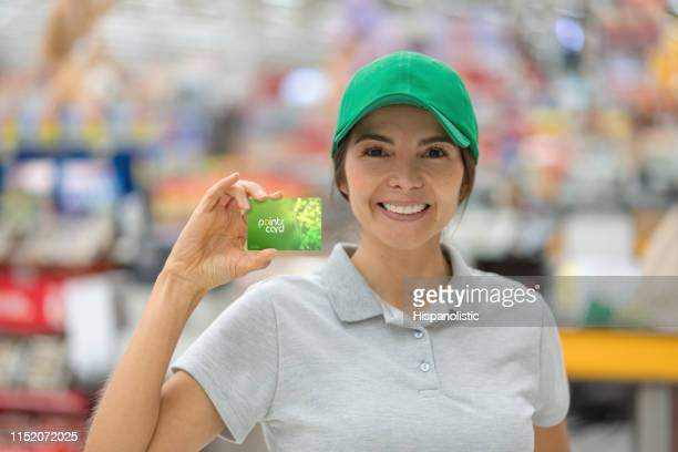 beautiful woman working at a supermarket holding a rewards program card while facing camera smiling - hispanolistic stock photos and pictures