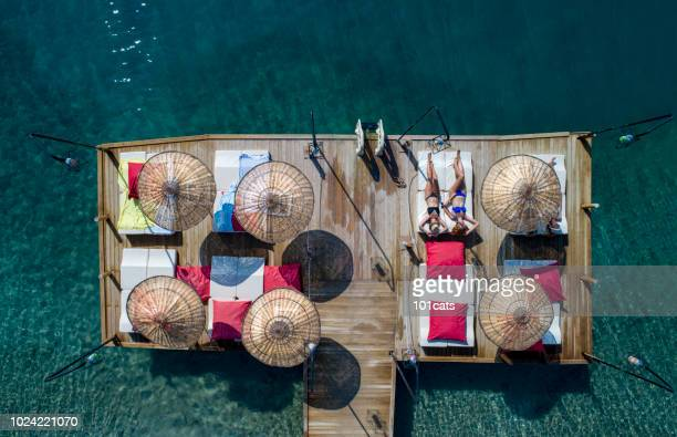 Beautiful womans sunbathing on a wooden pier in sea aerial photo