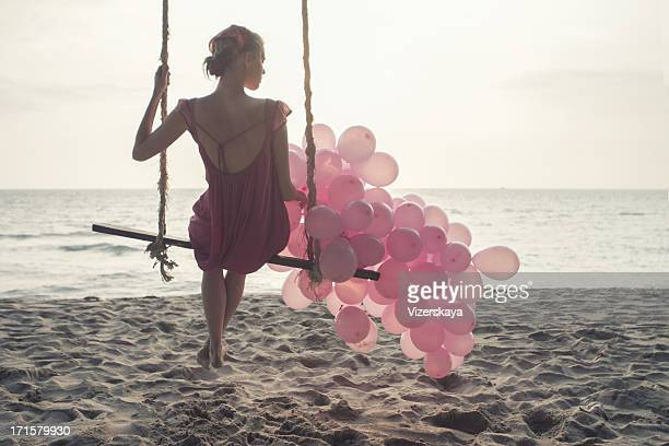 beautiful women at swing with pink ballons - pink dress stock photos and pictures