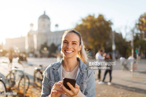 beautiful women holding phone and looking at camera - mid adult stock pictures, royalty-free photos & images