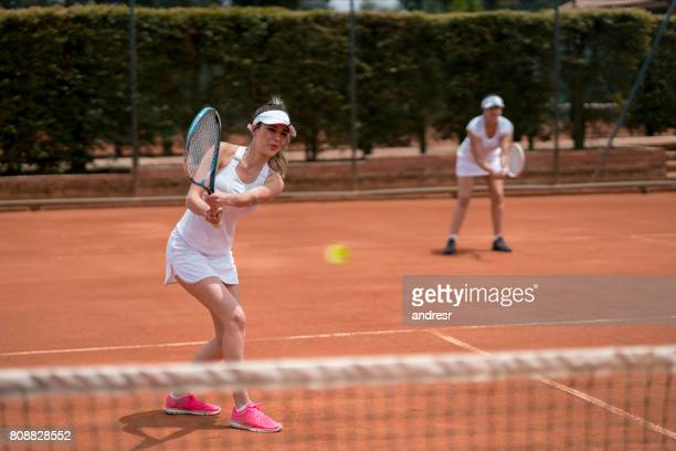 beautiful women playing doubles in tennis - doubles stock photos and pictures
