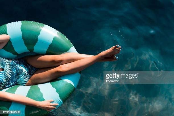 beautiful women relaxing in the pool while sitting on inflatable ring - swimming pool stock pictures, royalty-free photos & images