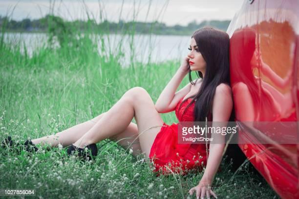 赤い車と赤いドレスで景色を眺めてリラックスできる美しい女性 - 赤のドレス ストックフォトと画像