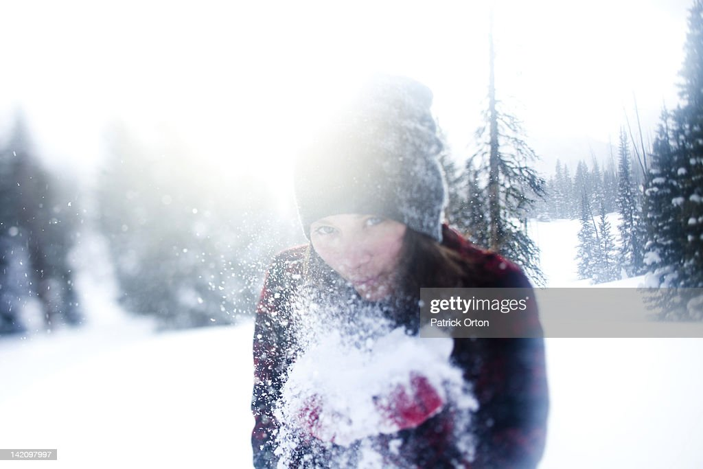 A beautiful women smiles while blowing snow at sunset in Wyoming. : Stock Photo