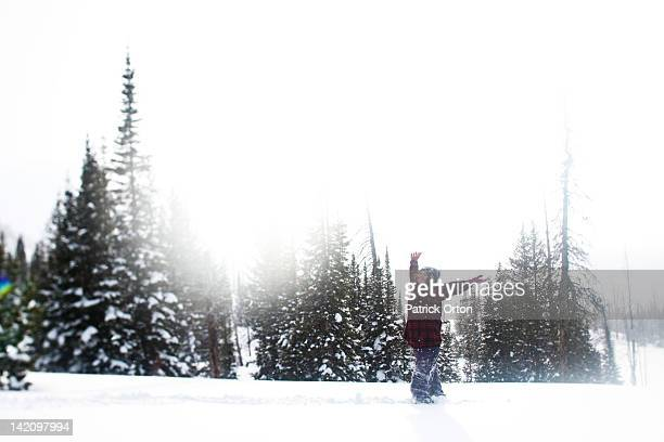 a beautiful women smiles while hiking through a pristine snow field at sunset in wyoming. - snowfield stock pictures, royalty-free photos & images