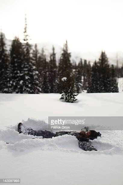 A beautiful women smiles while making a snow angel in a pristine field at sunset in Wyoming.