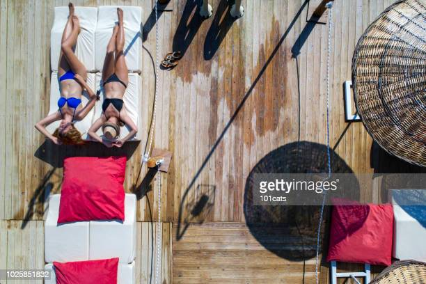 Beautiful women sunbathing on a wooden pier on sea. aerial view photo