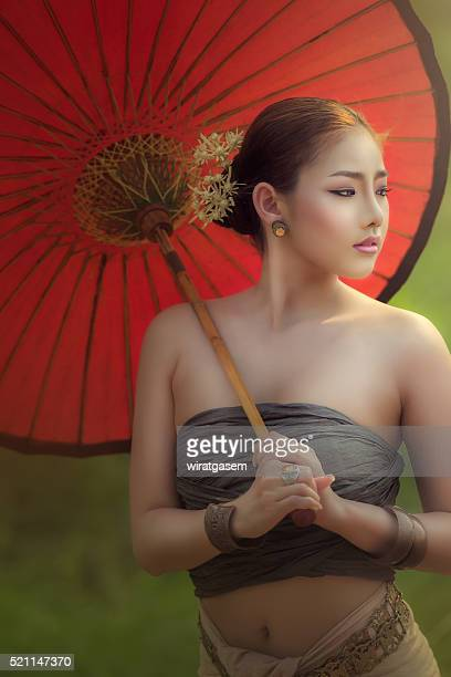 beautiful women wearing her traditional dress and hold red umbrella. - wiratgasem stock photos and pictures