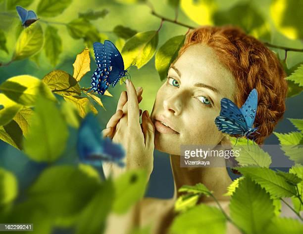 Schöne Frau mit Schmetterling in der Natur