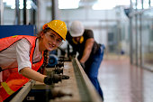 Beautiful worker or technician or engineer woman smile and look forward in front of rail of the machine with her co-worker as background in factory