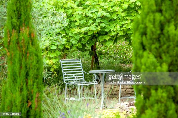 beautiful wrought iron, garden table and chairs in a garden hideaway with tall evergreen trees - chair stock pictures, royalty-free photos & images