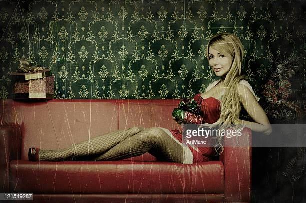 Beautiful Xmas woman laying on a sofa, intentionally aged