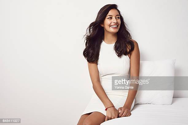 Beautiful youn woman sitting on her bed