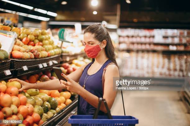 beautiful young adult caucasian woman in face mask shopping for healthy groceries while using smart phone,belo horizonte,state of minas gerais,brazil - helena price stock-fotos und bilder