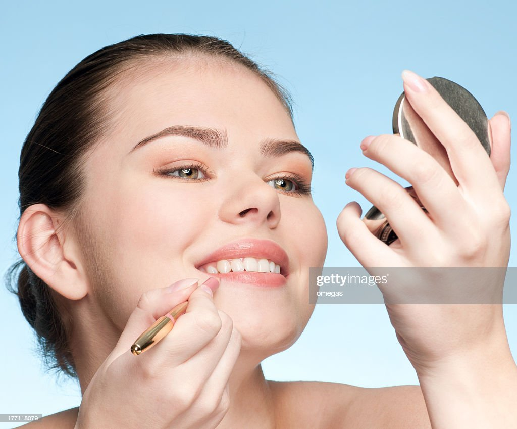 Beautiful young adult woman applying cosmetic lipstick pencil : Stock Photo