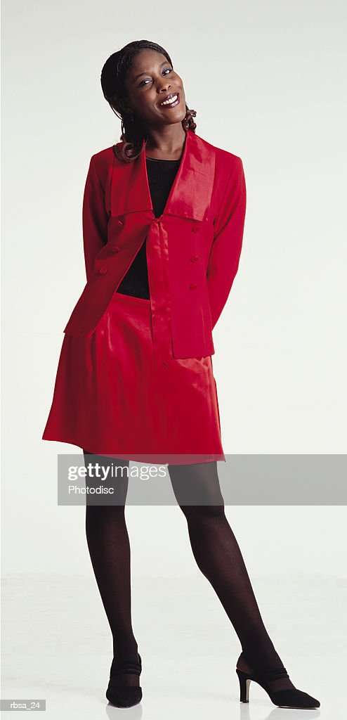 beautiful young african american adult female wearing a red plastic blazer and short red skirt stands in a perky pose while smiling at the camera : Foto de stock