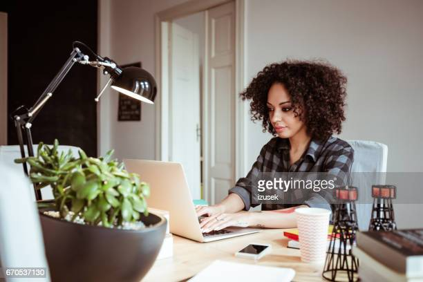 Beautiful young african woman working in home office