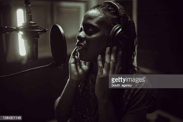 beautiful young african-american female singer recording song in the studio - soul music stock pictures, royalty-free photos & images