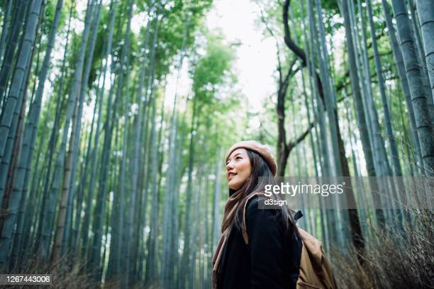beautiful young asian female backpacker enjoying in nature. she is walking along the pathway in the bamboo grove of arashiyama, kyoto, exploring and enjoying the spectacular nature scenics - travel foto e immagini stock