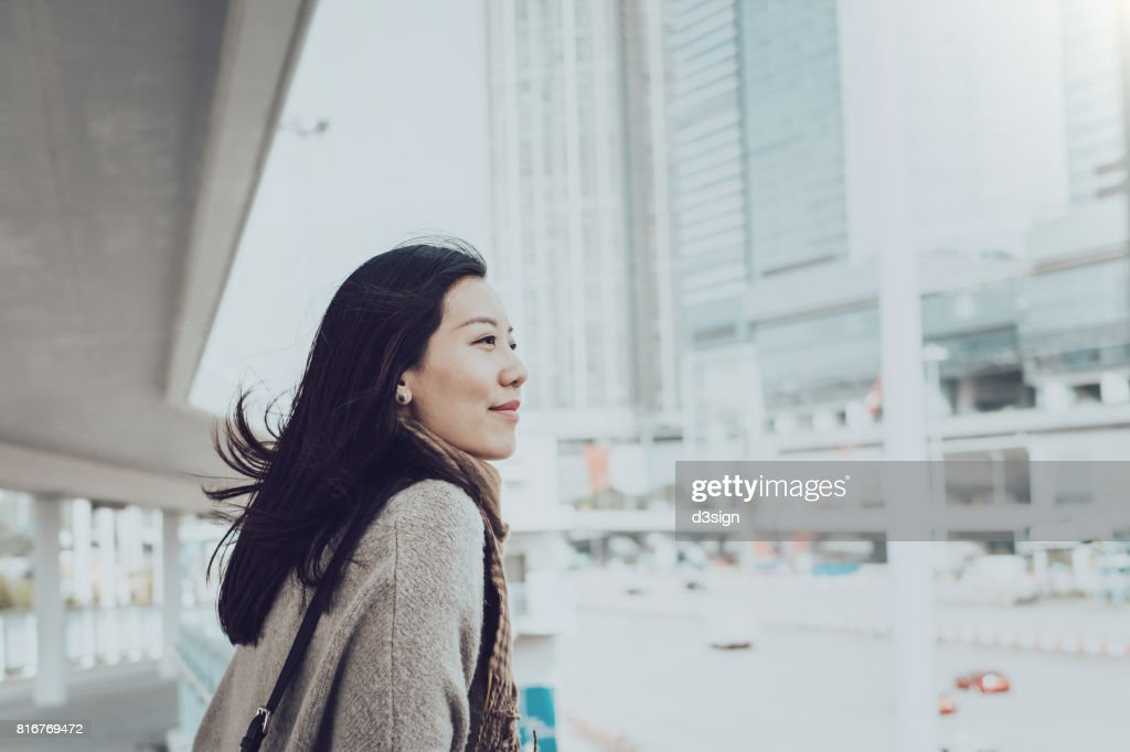 Beautiful young Asian lady overlooking cityscape of Hong Kong on urban bridge : Stock Photo
