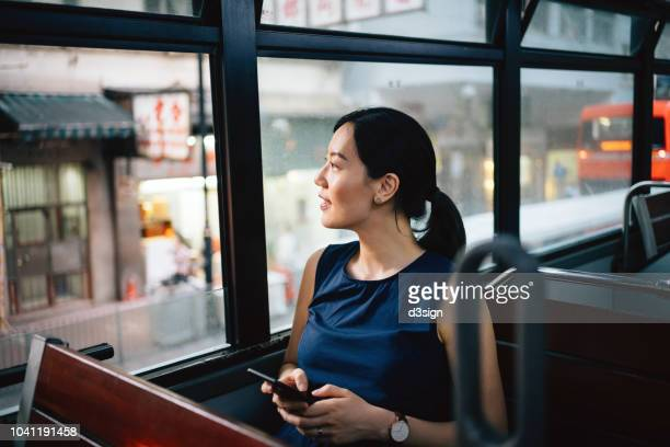 beautiful young asian lady with smartphone enjoying city scene through window while riding on public transportation in city - tram stockfoto's en -beelden