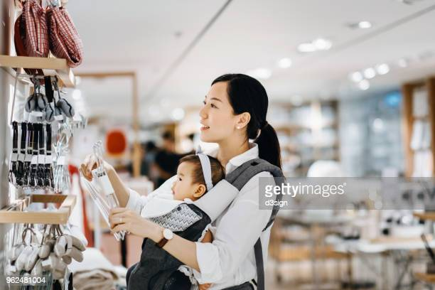 Beautiful young Asian mother carrying baby girl shopping for home essentials in shop
