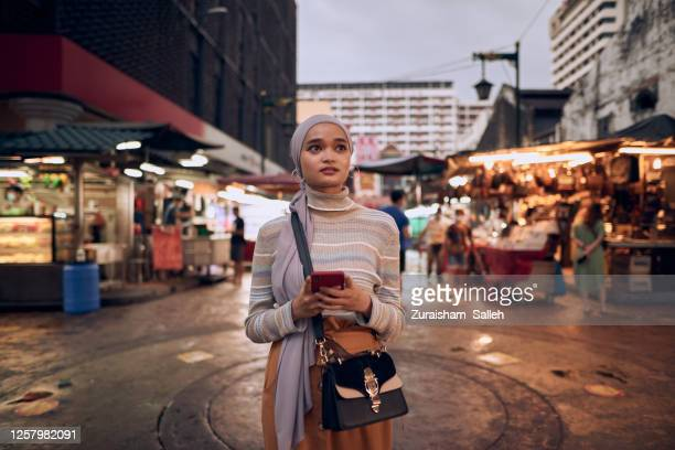 beautiful young asian muslim in hijab navigating using smart phone at street market outdoor - navigational equipment stock pictures, royalty-free photos & images