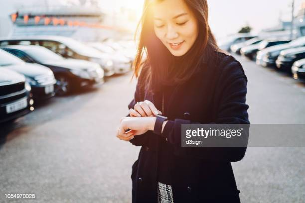 beautiful young asian woman checking time on smartwatch in city, in front of cars in outdoor carpark at sunset - premium access stock pictures, royalty-free photos & images