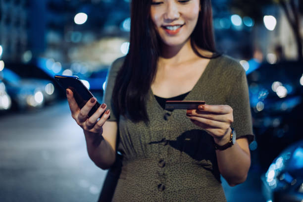 Beautiful young Asian woman doing online payment with smartphone and credit card in outdoor car park in the city, with illuminated street lights and blurred transportation in background