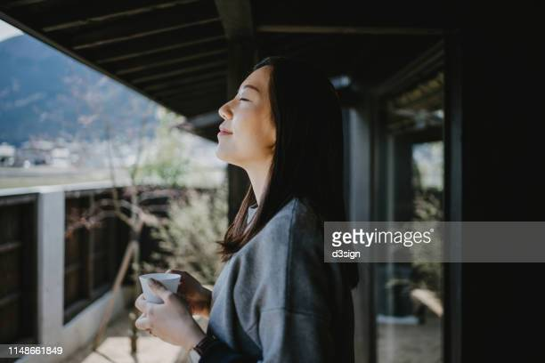 beautiful young asian woman drinking coffee and enjoying fresh air on balcony in the morning - kalmte stockfoto's en -beelden