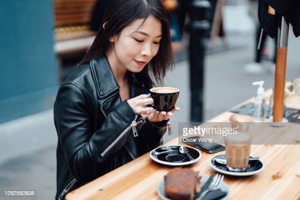 beautiful young asian woman enjoying coffee at sidewalk cafe - east asian ethnicity stock pictures, royalty-free photos & images