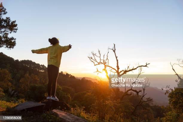 beautiful young asian woman enjoying fresh air on wild in the morning. - einfaches leben stock-fotos und bilder