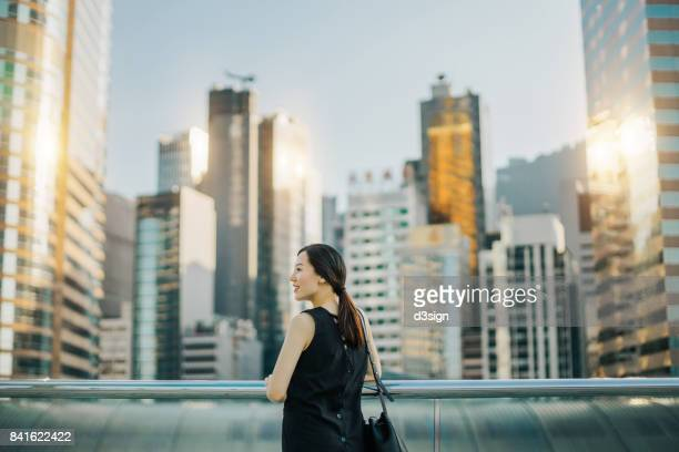 Beautiful young Asian woman enjoying the city view during sunset on urban balcony