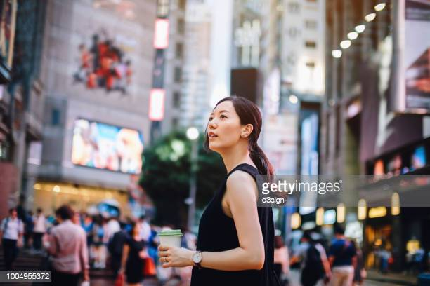 beautiful young asian woman holding coffee visiting and exploring in the busy downtown city street of hong kong - fashion hong kong stock photos and pictures
