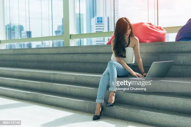 beautiful young asian woman is using a laptop and smiling while sitting on stairs - korean teen stock pictures, royalty-free photos & images