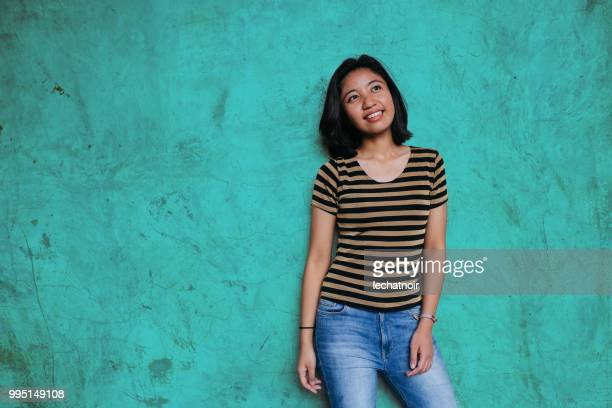 beautiful young asian woman leaning on a turquoise colored wall - mid length hair stock pictures, royalty-free photos & images