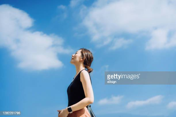beautiful young asian woman relaxing in the nature, taking a deep breath enjoying some fresh air and gentle wind breeze with eyes closed, against clear blue sky on a sunny day - 雰囲気 ストックフォトと画像