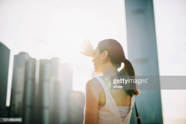 beautiful young asian woman shielding eyes from the sun flare while overlooking at city skyline - solar flare stock pictures, royalty-free photos & images