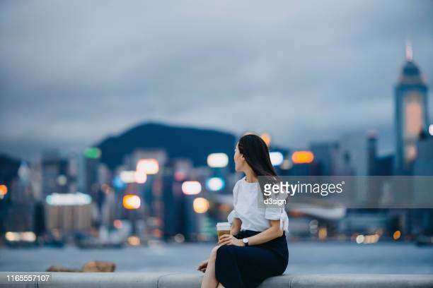 beautiful young asian woman sitting by the promenade of victoria harbour, having coffee and enjoying the spectacular urban city skyline at dusk - prosperity stock pictures, royalty-free photos & images