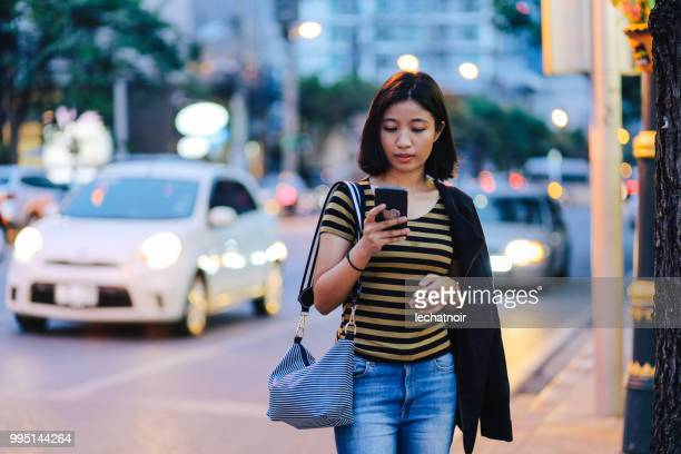 Beautiful young Asian woman texting on the street or just calling a cab