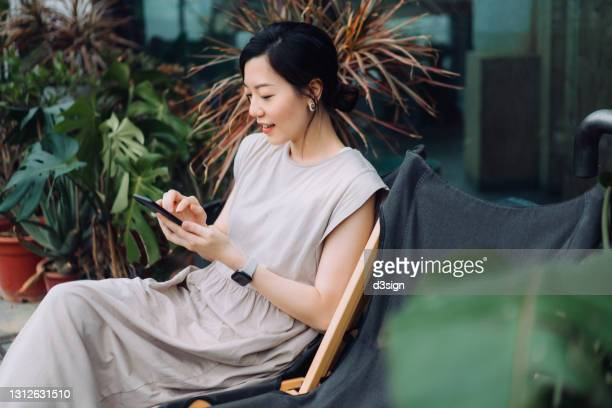 beautiful young asian woman using smartphone while relaxing on deck chair in the backyard, surrounded by beautiful houseplants. lifestyle and technology - facebook stock pictures, royalty-free photos & images