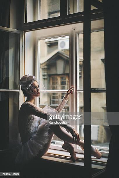 Beautiful young balerina looking trough the window