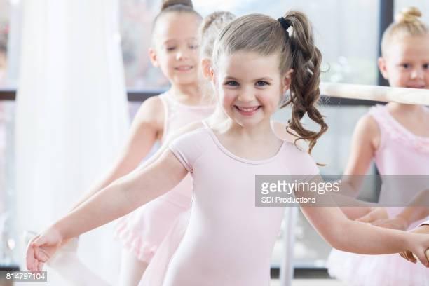 Beautiful young ballerina poses at ballet barre