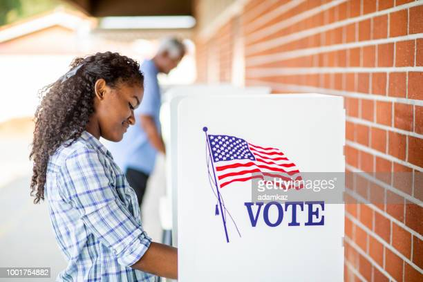 beautiful young black girl voting - votes for women stock photos and pictures