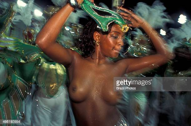 Beautiful young black nude woman dances samba in front of drummers at Samba schools parade Rio de Janeiro carnival Brazil