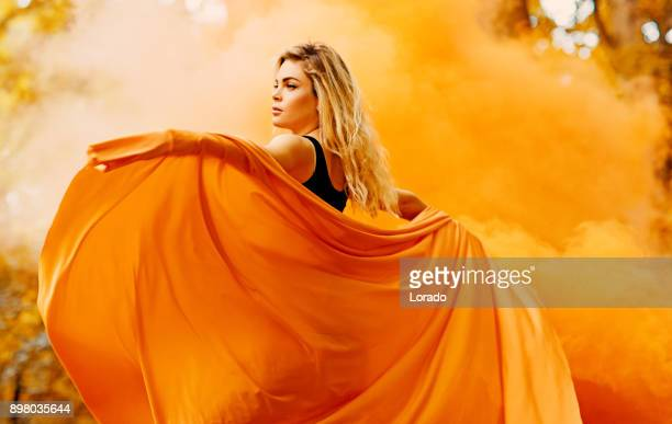 beautiful young blond female woman dancing and posing in orange smoke in outdoor countryside setting - explosives stock photos and pictures