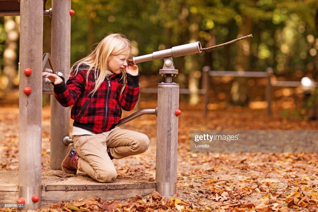 Schöne junge blonde Mädchen spielen in Autumnal Park : Stock-Foto