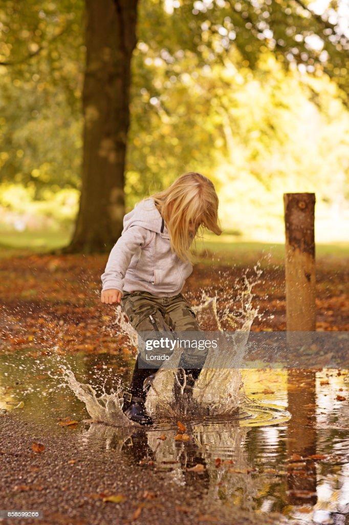 Schöne junge blonde Mädchen spielen in Pfützen in Autumnal Park : Stock-Foto